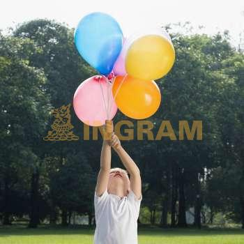 Boy holding balloons in a park