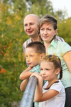 dad, mom, little boy and girl is lean elbow on bridge fence and looking away