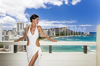 Hawaii, Oahu, Waikiki, Beautiful woman on hotel balcony overlooking Waikiki Beach and Diamond Head.