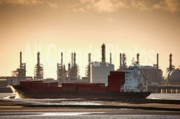 teesside, england; a boat in the water with a refinery in the background along the shore