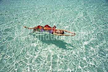 Woman floating in tropical ocean water.