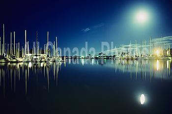 Hawaii, Oahu, Honolulu, Ala Wai Yacht Harbor, boats during moonrise, moon reflected on water.