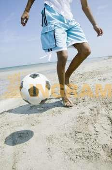Low section view of a teenage boy playing with a soccer ball on the beach
