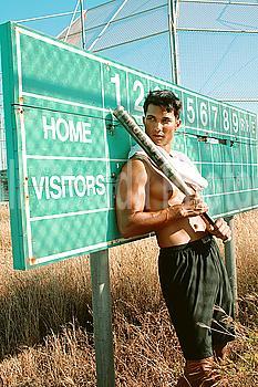 Hawaii, Oahu, Male leaning against old baseball field scoreboard with Bat in hands.